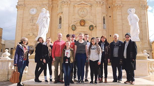 Alex Harding, fourth from left, with his fellow students in front of Our Lady of Victories parish church, Xagħra. First and second from right are Fr Giovanni Curmi and Fr Richard Ebejer respectively. Photo: Charles Spiteri