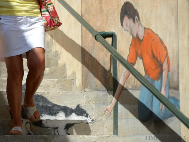 A lady walks over a 3D painting by artist Lewis Zammit on a on a set of stairs in Mellieha on August 6. . Photo: Matthew Mirabelli