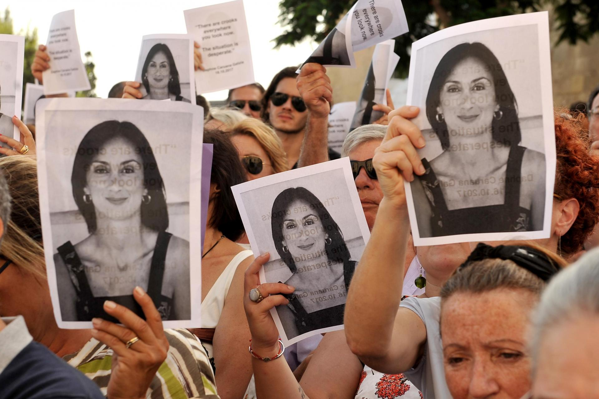 Activists hold up photos of Daphne Caruana Galizia. Ms Caruana Galizia was murdered in October 2017. Photo: Chris Sant Fournier