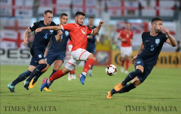 Malta's Jean Paul Farrugia (no 14) tries to make his way through the England defence during their FIFA 2018 World cup Qualifying Group F Match at the National Stadium in Ta'Qali on September 1. Photo: Matthew Mirabelli