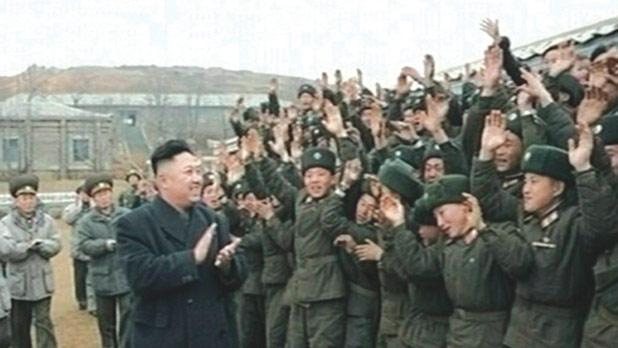 North Korean leader Kim Jong-un applauds as he is welcomed by members of the military at an undisclosed location.