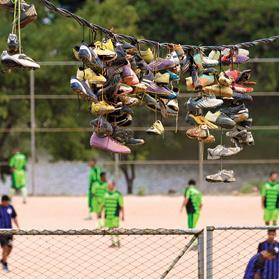 Discarded boots hang from an electric wire where they were thrown by their owners over several months after Sunday peladamatches in the Morro do Papagaio favela in Belo Horizonte. Photo: Washington Alves/Reuters