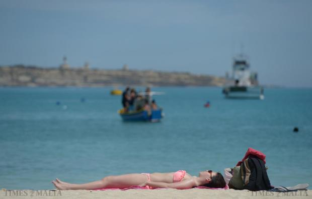 A lady sunbathes at Pretty Bay in Birzebbugia on May 3. Photo: Matthew Mirabelli