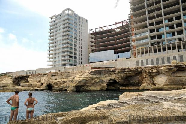A couple of bathers watch the ongoing high-rise construction from what used to be the popular Tigne Beach resort in Sliema on August 18. Photo: Chris Sant Fournier