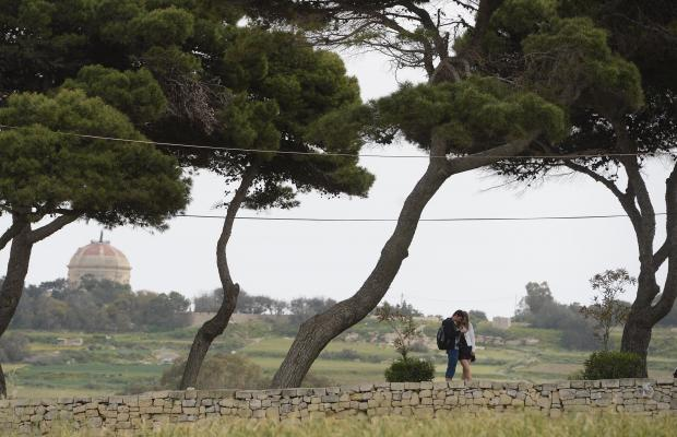 A couple wait for a bus on the outskirts of Mdina on April 10. Photo: Matthew Mirabelli