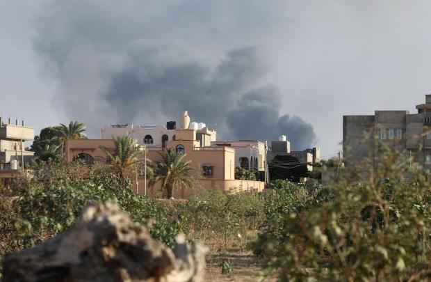 Smoke rises during heavy clashes between rival factions in Tripoli.