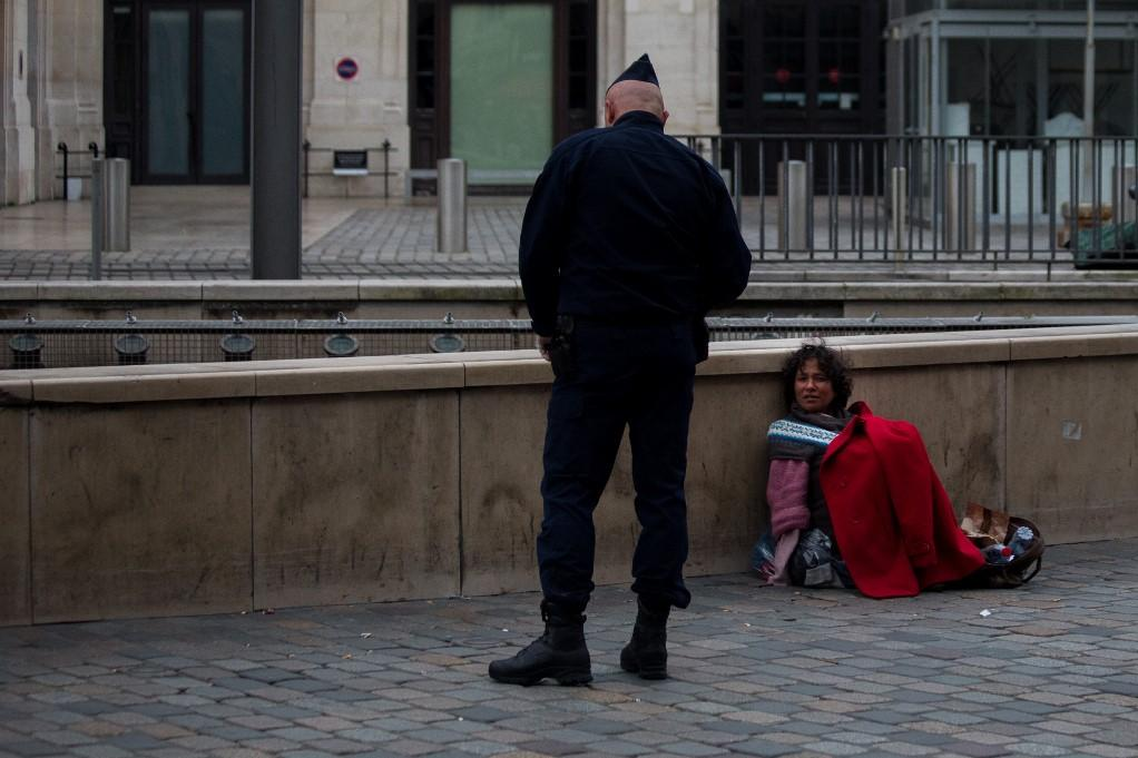 A French police officers checks up on a homeless person in Bordeaux. Photo: AFP