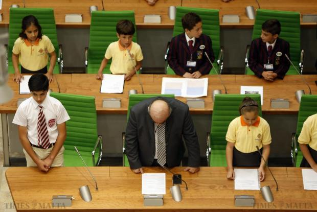 Schoolchildren and Foreign Minister George Vella (centre) rise from their seats for an opening prayer during their annual parliamentary session of EkoSkola, held in Parliament House in Valletta on May 27. The activity gives students the opportunity to meet MPs and discuss their environmental concerns. Photo: Darrin Zammit Lupi