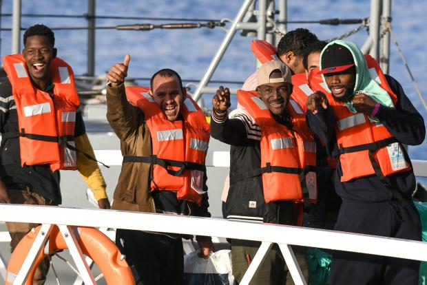 Migrants wave after being allowed to disembark in Malta last week.