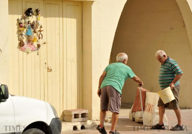 Two elderly people stop for a chat in a Marsaxlokk street on October 19. Photo: Chris Sant Fournier