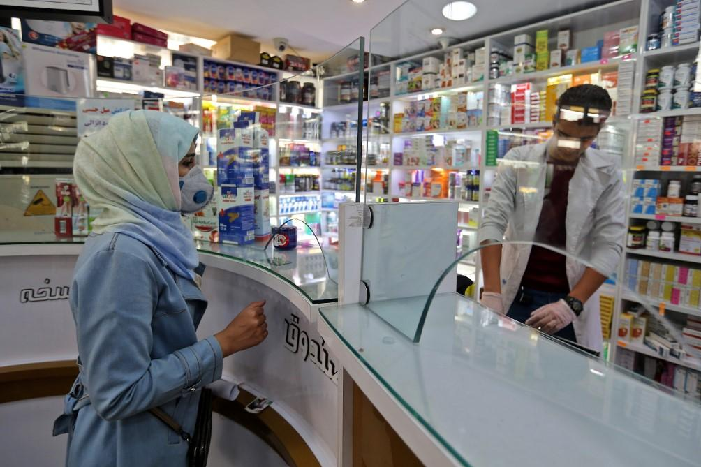 A woman wears a face mask as she shops at a pharmacy in Tehran, Iran. Photo: AFP