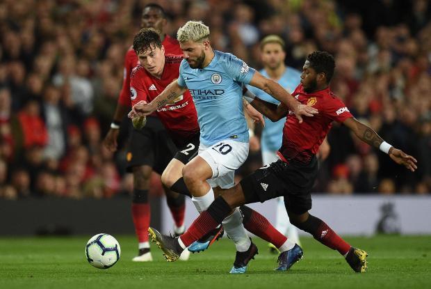 Man. City's Sergio Aguero (centre) beats Man. Utd players' pressure to advance at goal.