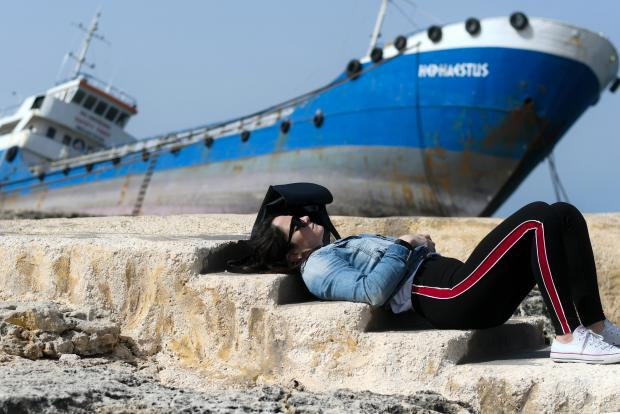 A woman sunbathes in Qawra as the 885-tonne Hephaestus, which ran aground in stormy seas last month, remains embedded in the rocks. March 4. Photo: Jonathan Borg