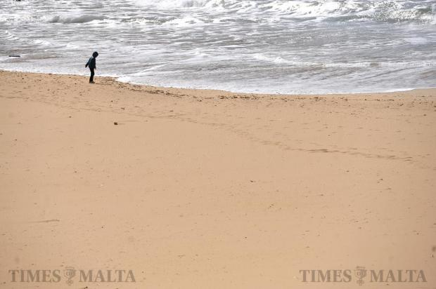 A boy stands at the water's edge at Golden Bay on February 18. Photo: Chris Sant Fournier