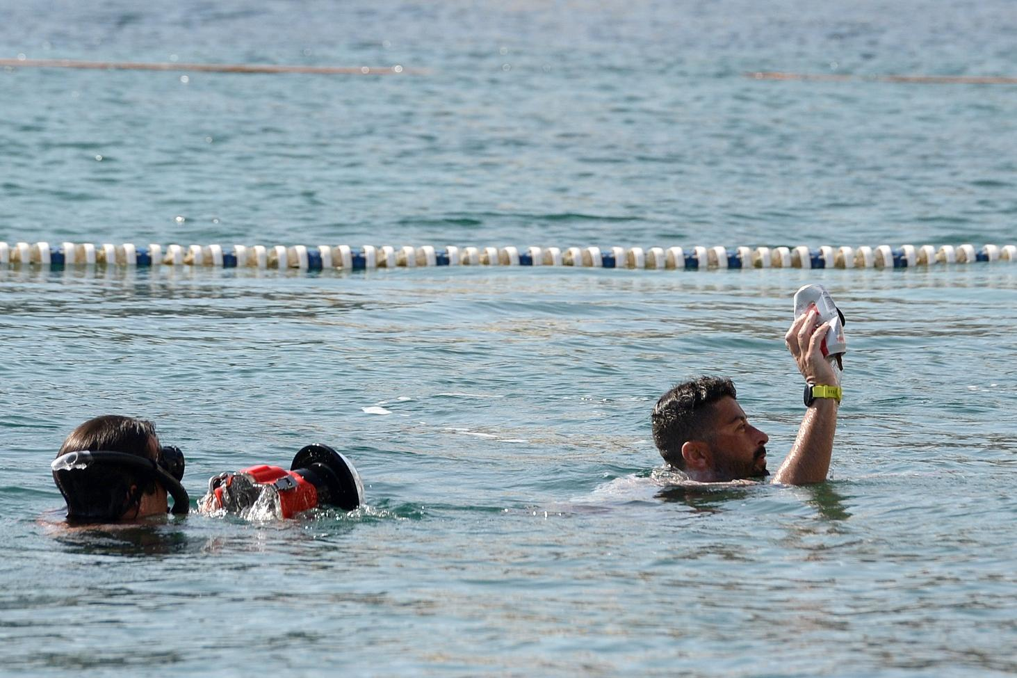 Neil Agius picks up rubbsh from the sea as he completes his swim in Balluta Bay on Friday morning. Photo: Matthew Mirabelli