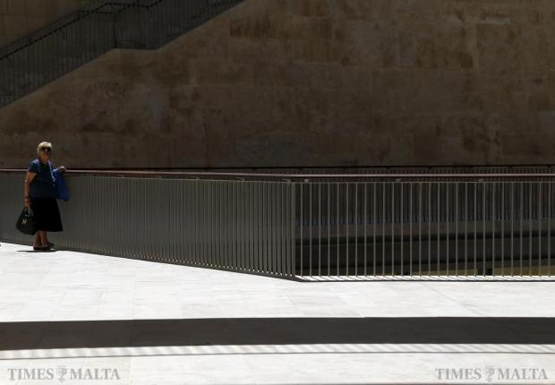 A woman walks between the buildings of Parliament House in Valletta on May 12. Photo: Darrin Zammit Lupi