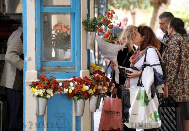 A woman buys fresh flowers in Valletta on November 16. Photo: Chris Sant Fournier