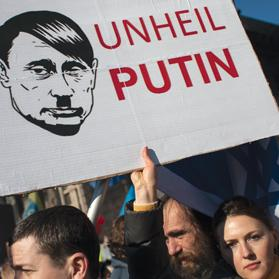 A woman holds a sign depicting Russian President Vladimir Putin as Adolf Hitler as she attends a rally at Independence Square in Kiev, Ukraine, yesterday. Photo: Reuters