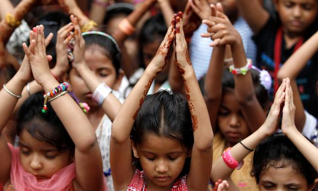 School children in Ahmedabad, India pray for the victims. Photo: Amit Dave/Reuters