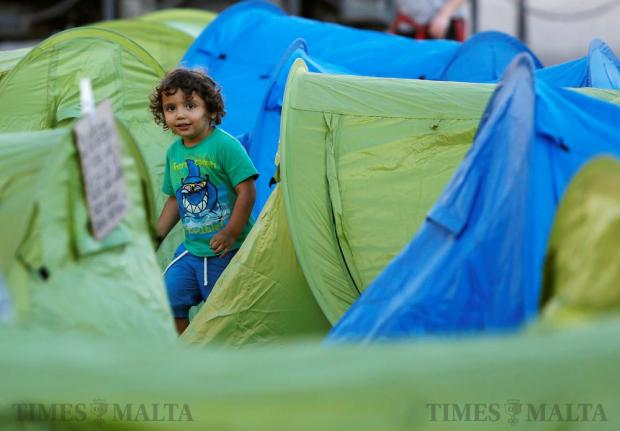 A child walks among tents in a camp set up by environmental activists protesting against what they say is over-development throughout the Maltese islands, in front of the Auberge de Castille housing the Office of the Prime Minister in Valletta on May 14. Photo: Darrin Zammit Lupi