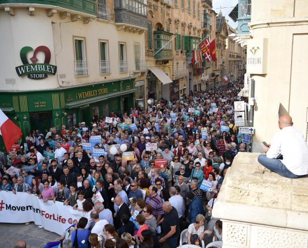 A man sits on top of the theatre in Valletta to watch a protest against a bill introducing embryo freezing in Valletta on April 22. Photo: Mark Zammit Cordina