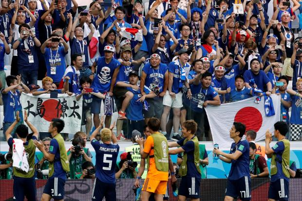 Japan players celebrate with their fans after reaching the knock-out stages.