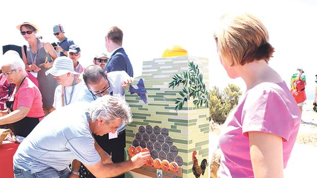 One of the delegates placing a mosaic orange on the monument watched by Gozo Minister Justyne Caruana (right). Photos: Charles Spiteri