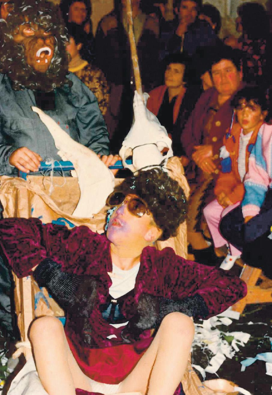 A participant dressed as a woman being pushed around in a trolley with animal skulls.