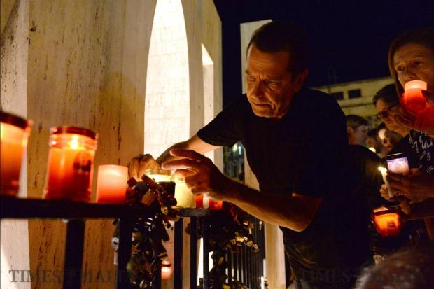A man lights a candle during a candlelight vigil in Sliema, on October 16, in tribute to late journalist Daphne Caruana Galizia who was killed by a car bomb close to her home in Bidnija. Photo: Matthew Mirabelli