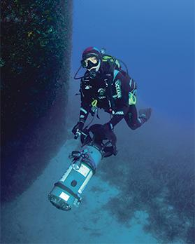 A diver surveys a cave using a sea scooter.