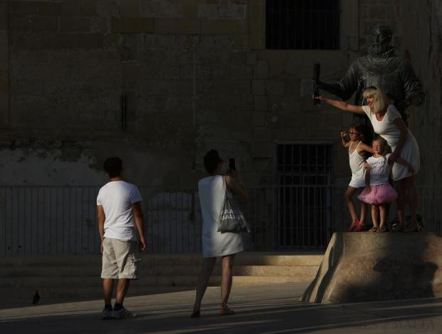 Tourists pose for a picture on the statue of Grandmaster Jean Parisot De Valette in Valletta on July 13. Photo: Darrin Zammit Lupi