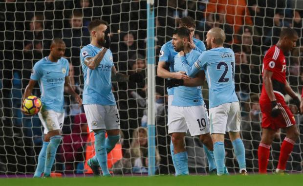 Manchester City's Sergio Aguero celebrates scoring their third goal with team mates.