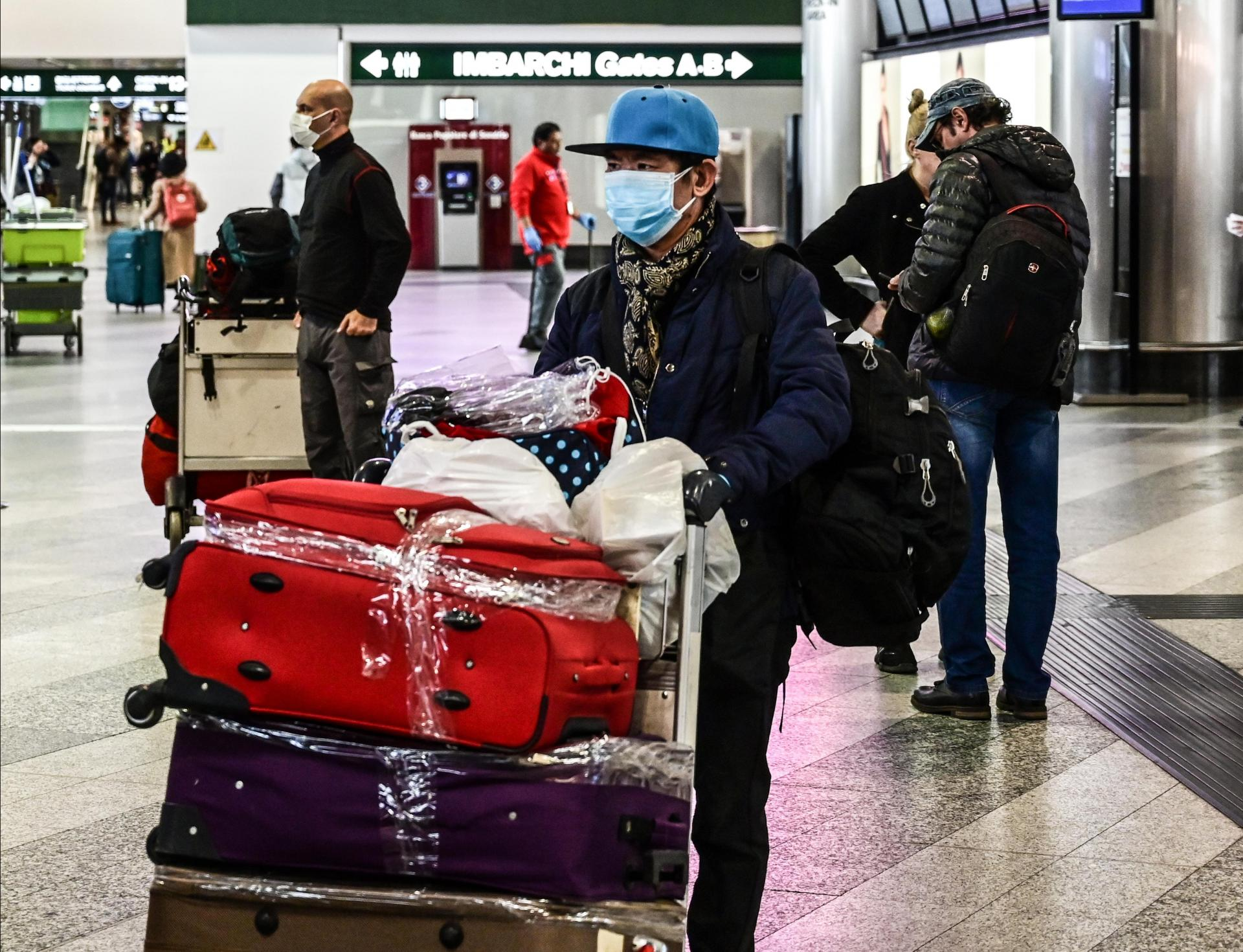 A passenger wearing a respiratory mask goes to check in at a terminal of Milan-Malpensa airport. Photo: AFP