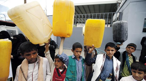 Boys hold up jerrycans to be filled with water outside the United Nations' offices in Sanaa, Yemen. Photos: Reuters
