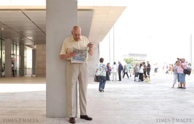 A man reads a newspaper by one of the columns of the Parliament in Valletta on June 6. Photo: Chris Sant Fournier