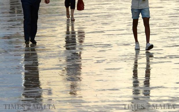 People make their way down Republic Street in Valletta after a brief rainstorm on August 25. Photo: Matthew Mirabelli