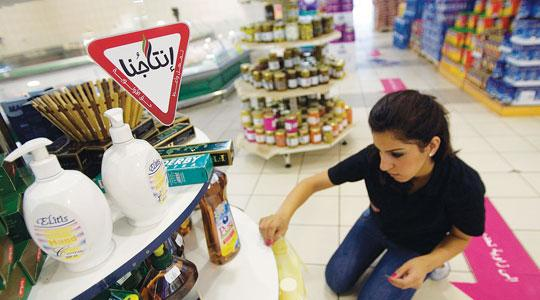 A Palestinian worker sticks Intajuna (our products) stickers on Palestinian goods displayed in a supermarket in the West Bank city of Ramallah.