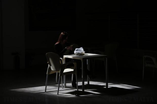 An officer worker is caught in a shaft of sunlight during her lunch break at a Valletta office on March 6. Photo: Darrin Zammit Lupi