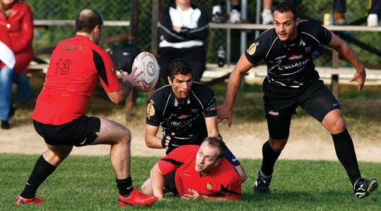 Stompers' Chris Morton offloads the ball to Malcolm Attard (left) after being tackled by Sean Doublesin, of Kavallieri.
