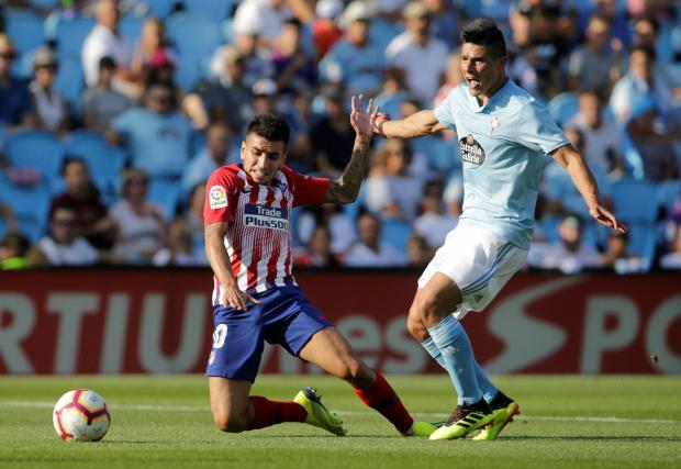 Atletico Madrid's Angel Correa falls under the challenge of Celta Vigo's Facundo Roncaglia.