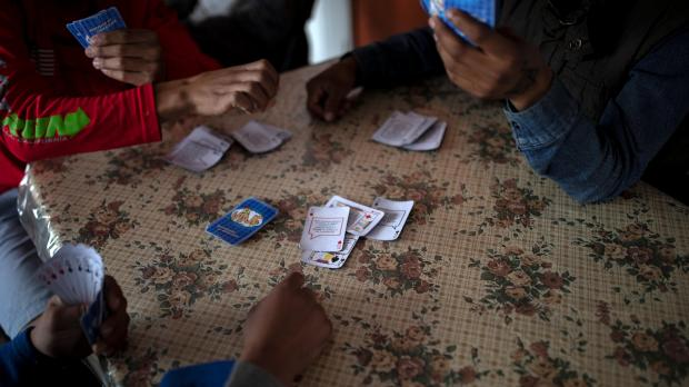 Teenage boys play a game of cards at a migrant shelter for unaccompanied minors.