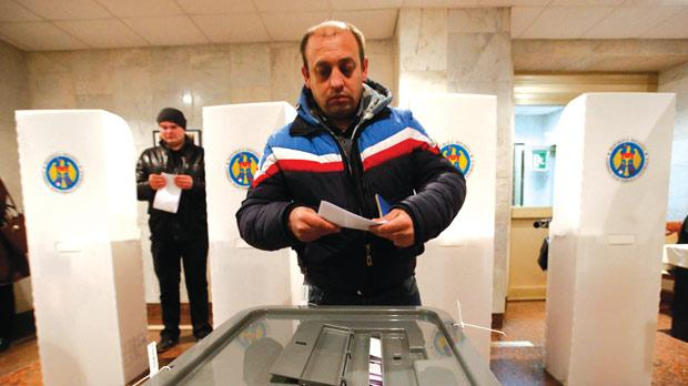 A man casting a ballot during a parliamentary election at a polling station at the Moldovan embassy in Moscow, Russia, yesterday.