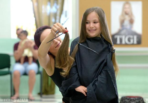 Five-year-old Aurora De Luca smiles as her long hair is cut during the 'Dare with your hair' event at the Msida Primary School on June 28. The collected hair will be made into wigs for those who have experienced hair loss due to a medical condition. Photo: Matthew Mirabelli