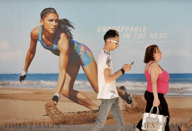 People walk past an advertising poster at The Point in Sliema on June 6. Photo: Chris Sant Fournier