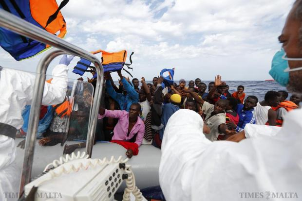 Rescuers of the NGO Migrant Offshore Aid Station (Moas) toss lifejackets to a group of 106 sub-Saharan Africans on board a rubber dinghy off the Libyan coast on October 4. Photo: Darrin Zammit Lupi/Moas