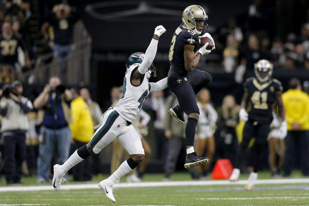 Michael Thomas #13 of the New Orleans Saints makes the catch under pressure from Josh Hawkins #48 of the Philadelphia Eagles.