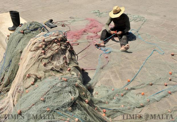 A man fixes fishing nets in Marsaxlokk on April 18. Photo: Chris Sant Fournier