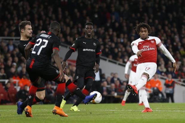 Arsenal's Nigerian striker Alex Iwobi (right) takes a shot.