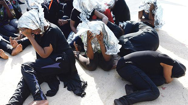 Migrants sit at a naval base after being rescued by Libyan coast guards in Tripoli, Libya. Picture was taken on June 18. Photo: Ismail Zitouny/Reuters