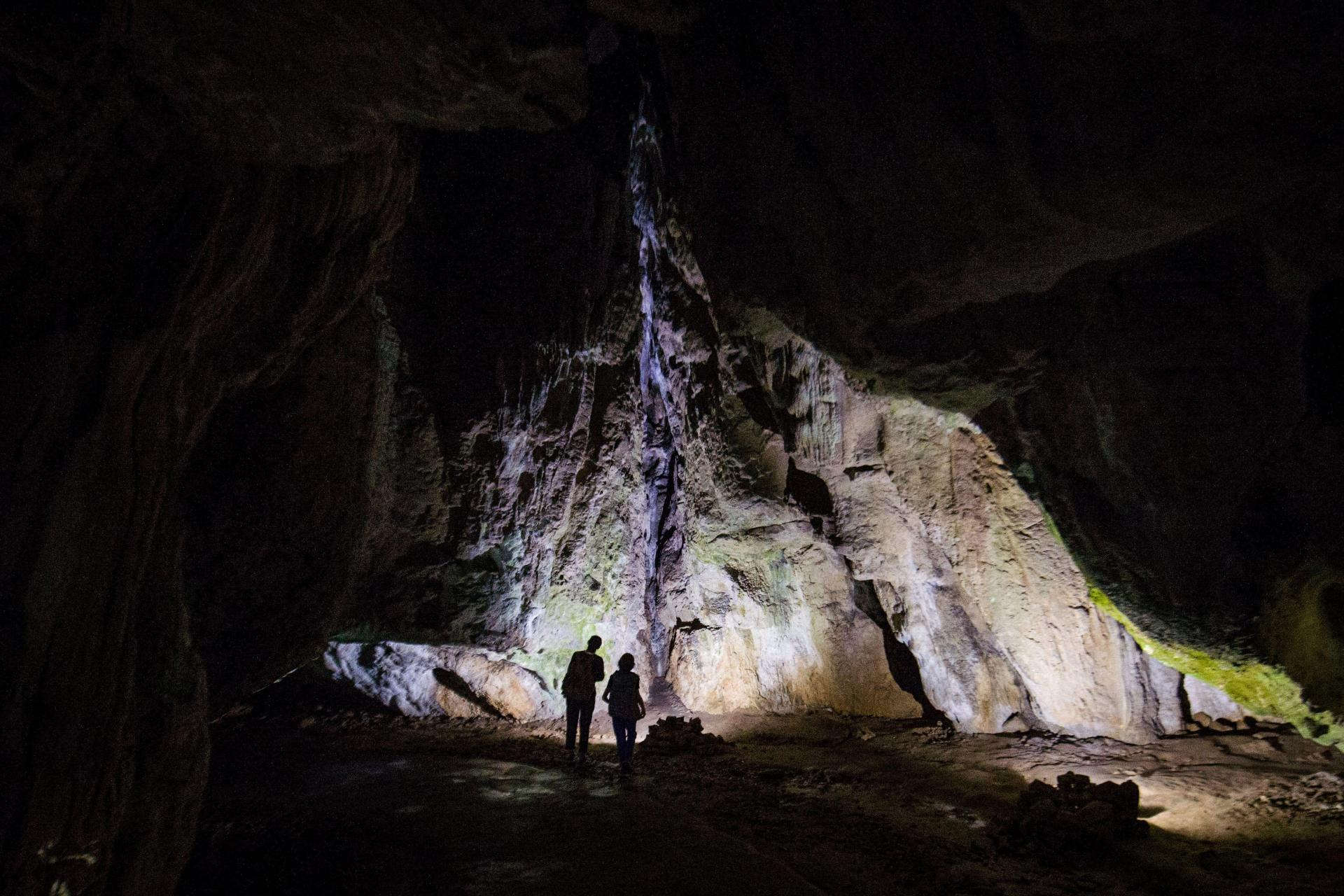 A local guide and visitors walk in the site of the Bacho Kiro Cave, near the city of Dryanovo, northern Bulgaria, on May 13, 2020. Photo: AFP